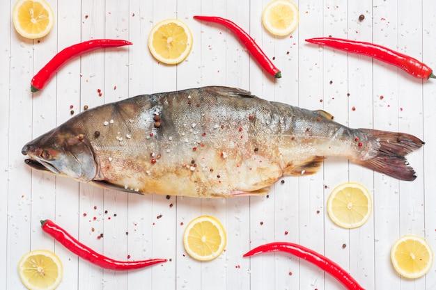 Pesce salmone rosa crudo con spezie, limone e peperoncino su un tavolo luminoso.
