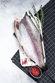 Pesce trota iridea fresco marinato con sale e timo. sfondo grigio.