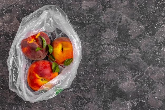 Pesche con un ramo di un albero in un sacchetto di plastica trasparente