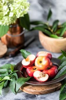 Pesche di frutta fresca con foglie su un primo piano piatto.