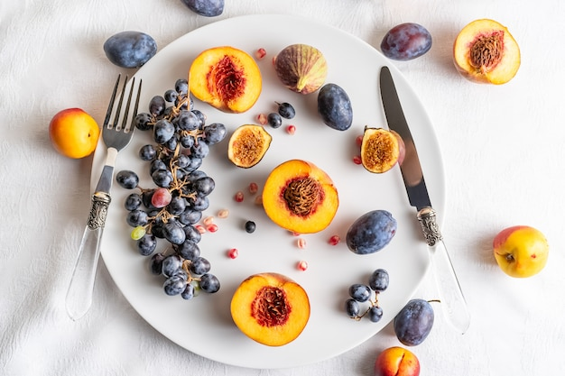 Pesche divise in due con le nettarine e l'uva sul piatto bianco