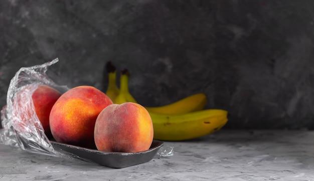 Pesche fresche in un contenitore di plastica e banane