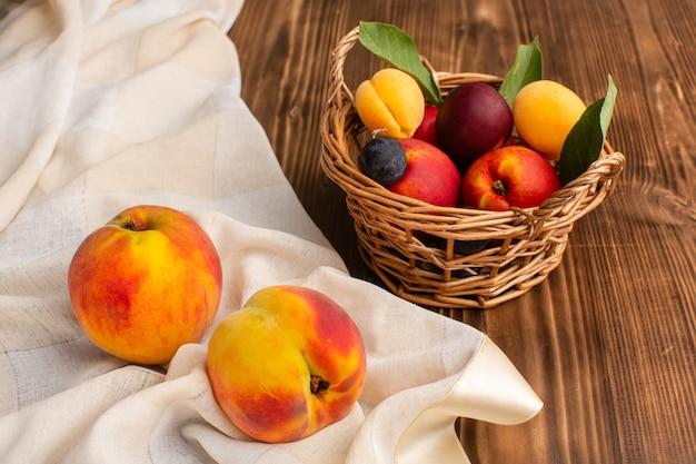 Pesche fresche insieme a cesto pieno di albicocche e prugne su legno