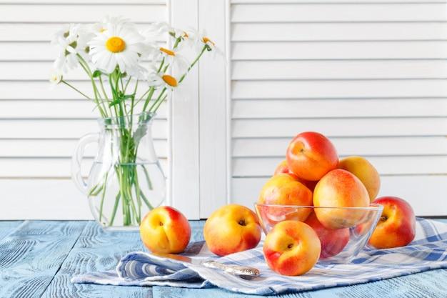 Pesche mature fresche in ciotola sulla tavola di legno blu e margherita in vaso