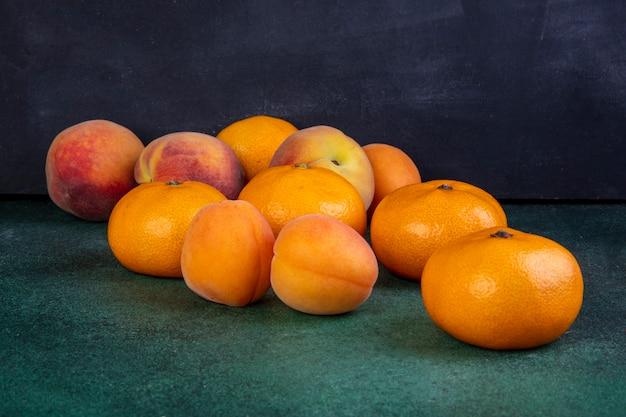 Pesche vista frontale con mandarini e albicocche