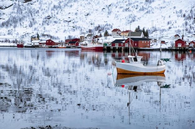 Peschereccio che galleggia e riflessione sulla spiaggia nel villaggio scandinavo