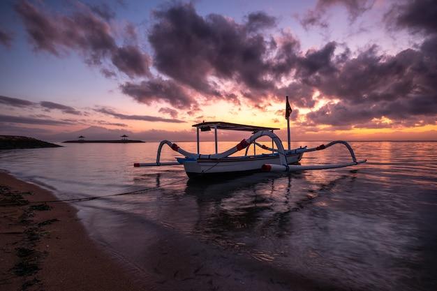 Peschereccio di jukung tradizionale antico sulla spiaggia all'alba variopinta
