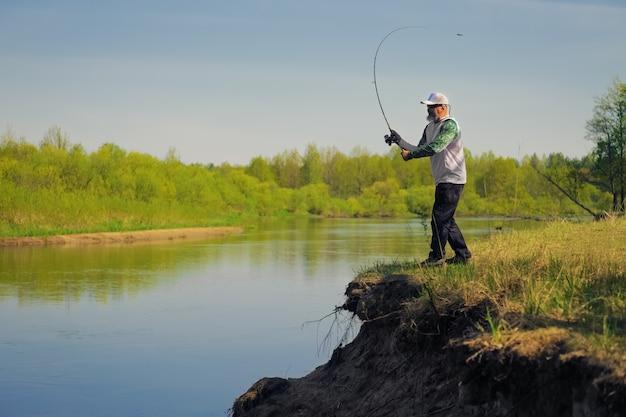 Pesci dell'uomo con la filatura sulla sponda del fiume
