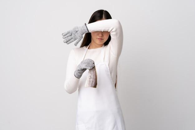 Pescivendolo cinese che indossa un grembiule e che tiene un pesce crudo sopra la copertura bianca della parete osserva a mano