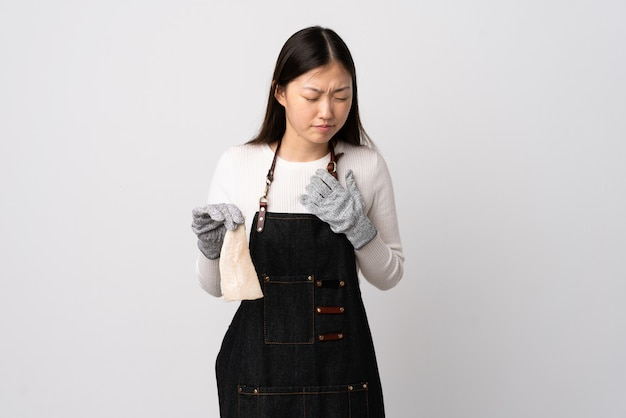 Pescivendolo cinese che indossa un grembiule e che tiene un pesce crudo sopra la parete bianca che ha un dolore nel cuore