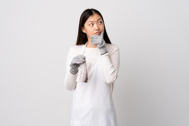 Pescivendolo cinese che indossa un grembiule e che tiene un pesce crudo sopra la parete bianca isolata che ha dubbi e con l'espressione confusa del fronte