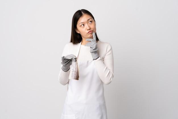 Pescivendolo cinese che indossa un grembiule e che tiene un pesce crudo sopra la parete bianca isolata che ha dubbi mentre cercando