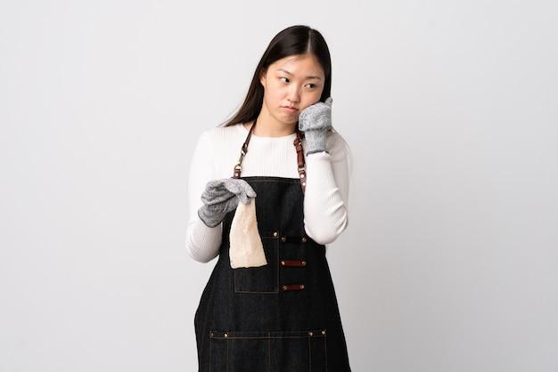 Pescivendolo cinese che indossa un grembiule e che tiene un pesce crudo sopra la parete bianca isolata con l'espressione stanca e annoiata