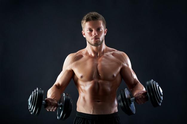 Pesi di sollevamento muscolari del giovane su fondo nero