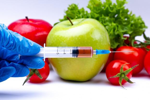 Pesticidi e nitrati vengono iniettati in frutta e verdura con una siringa. concetto di ogm e organismo geneticamente modificato. prodotti sani e naturali senza ogm senza additivi chimici.