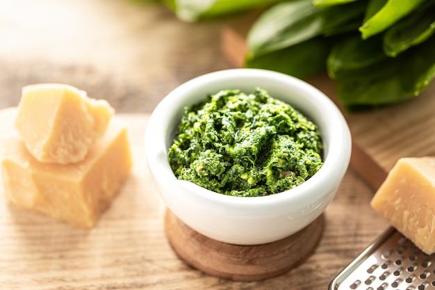 Pesto di porri selvatici con olio d'oliva e parmigiano in un mortaio di ceramica bianca su un tavolo di legno. proprietà utili di aglio orsino.
