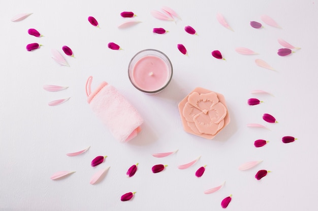 Petali di fiori attorno al morbido tovagliolo arrotolato; candela e sapone su sfondo bianco
