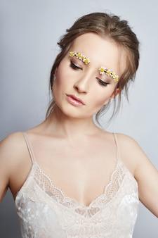 Petali di fiori sul viso ragazza, cosmetici donna
