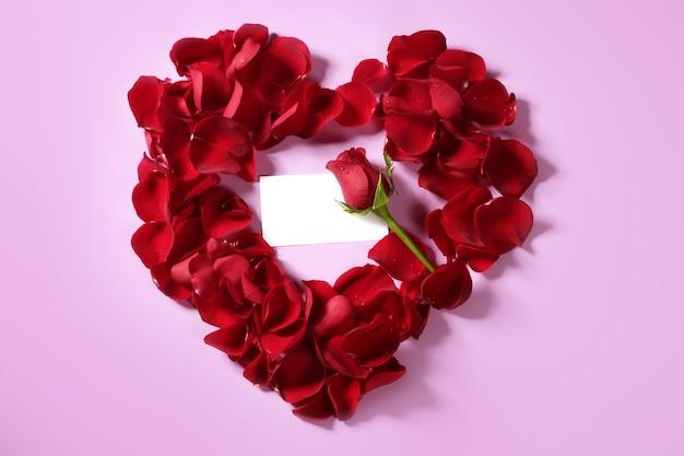Petali di rosa rossa nella forma del cuore, nota dello spazio in bianco della copia