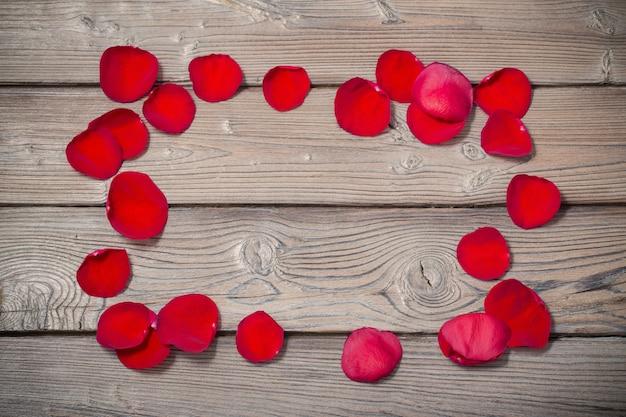 Petalo di rose rosse su fondo di legno