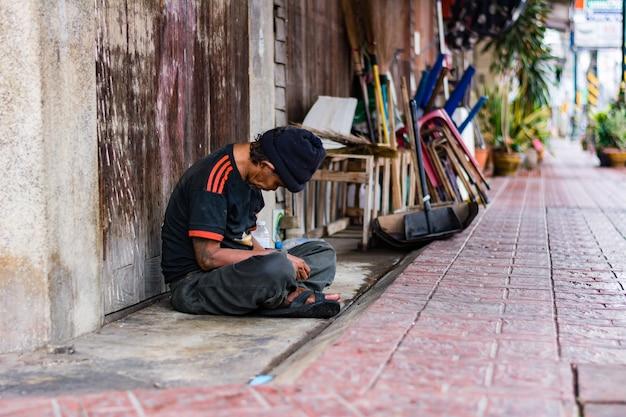 Petchburee, tailandia - 27 febbraio 2018: uomo del mendicante che dorme accanto al marciapiede per soldi sulla via