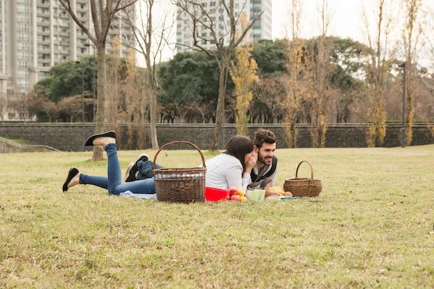 Pettegolezzo della giovane donna nell'orecchio del ragazzo che si trova sulla coperta nel parco