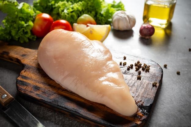 Petti di pollo crudi sul tagliere di legno.