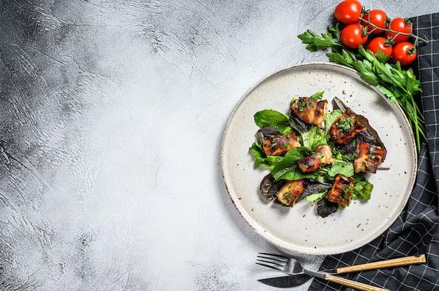 Petti di pollo ripieni, filetti di pancetta arrotolati con insalata verde. sfondo grigio
