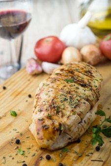 Petti di pollo sani alla griglia marinati cotti su un barbecue estivo e serviti con erbe fresche e succo di limone su una tavola di legno