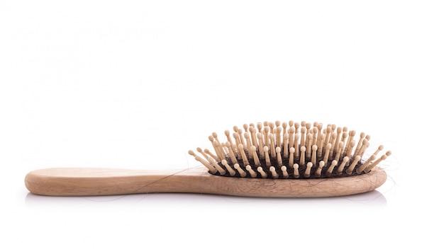 Pettine di legno con il colpo dello studio di problema di perdita di capelli neri ed isolato su bianco