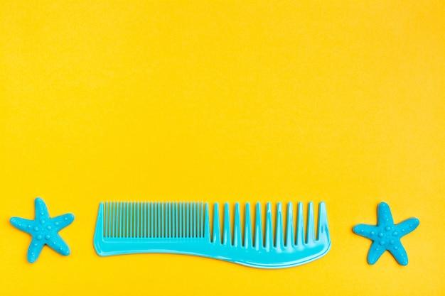 Pettine di plastica e due forcine per capelli sotto forma di una stella marina su una vista superiore gialla