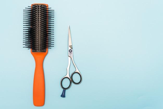 Pettine e forbici professionali neri. strumenti di parrucchiere su uno sfondo blu pastello