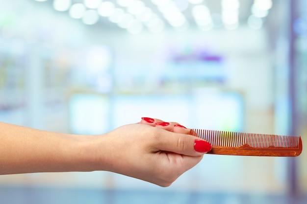 Pettine femminile del barbiere della tenuta della mano in deposito cosmetico