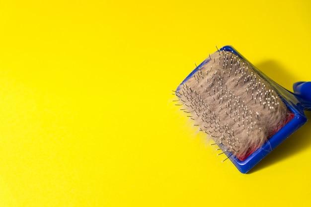 Pettine per peli di animali e lana grigia su un tavolo giallo. spazzola per animali.