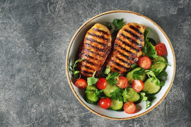 Petto di pollo alla griglia con insalata di pomodorini, cetrioli, rucola e prezzemolo