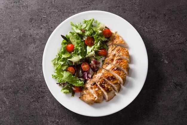 Petto di pollo arrostito con le verdure su un piatto sulla vista superiore nera
