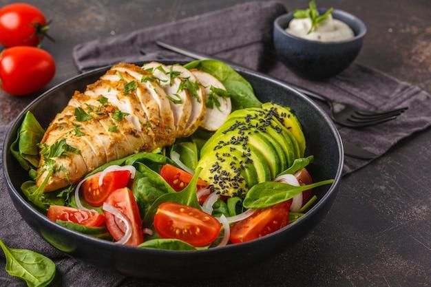 Petto di pollo e insalata di avocado con spinaci, pomodori e salsa caesar, sfondo scuro.
