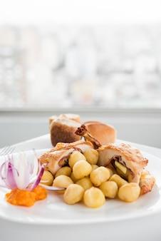 Petto di pollo farcito con gnocchi sul piatto bianco
