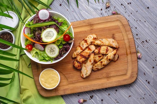 Petto di pollo grigliato affettato vista dall'alto con insalata di verdure e salsa sul tavolo