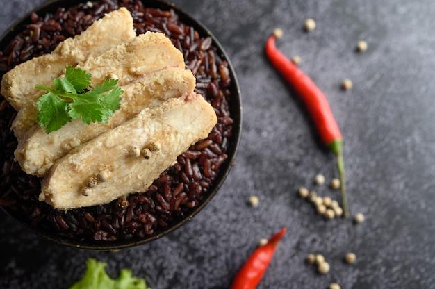 Petto di pollo grigliato condito con pepe su bacche di riso viola mature.