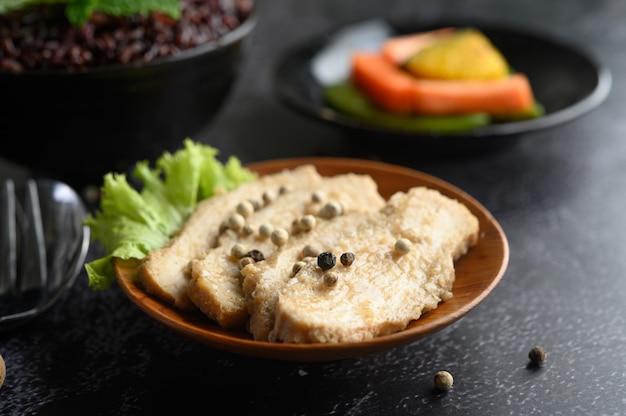 Petto di pollo grigliato, cosparso di pepe, posto su un piatto di legno