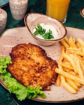 Petto di pollo grigliato e servito con patatine fritte, maionese e lattuga.