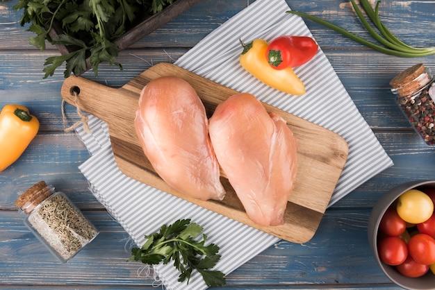 Petto di pollo piatto disteso su tavola di legno con ingredienti