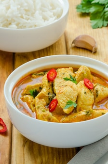 Petto di pollo piccante in salsa di curry gialla con aglio e peperoncino con riso bollito in una ciotola su una tavola di legno.