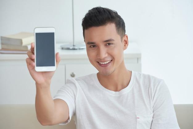 Petto sul colpo del ragazzo asiatico che mostra uno schermo del suo smartphone e sorridente