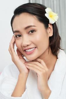 Petto sul colpo di una bella ragazza asiatica che tocca il suo viso perfetto con un fiore tra i capelli