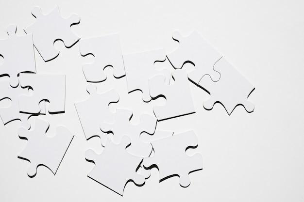 Pezzi bianchi di puzzle isolati su superficie bianca