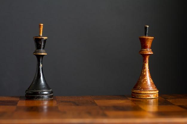 Pezzi degli scacchi in legno d'epoca su una vecchia scacchiera.