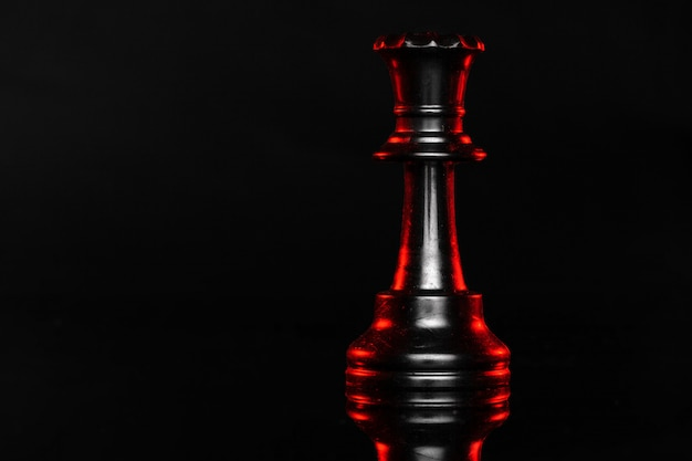 Pezzi degli scacchi su fondo scuro con la fine rossa della lampadina su