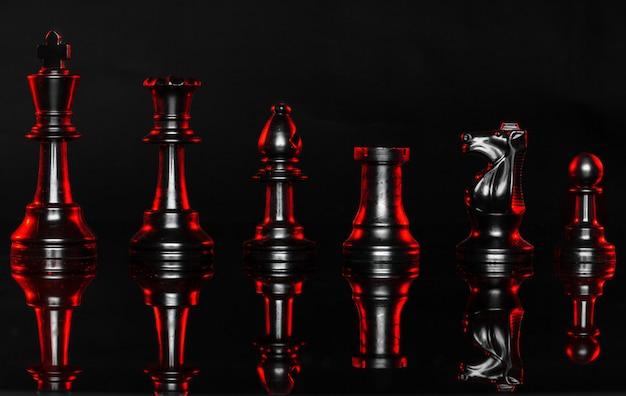 Pezzi degli scacchi su sfondo scuro con retroilluminazione rossa